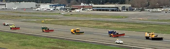 five snowplows on airport runway