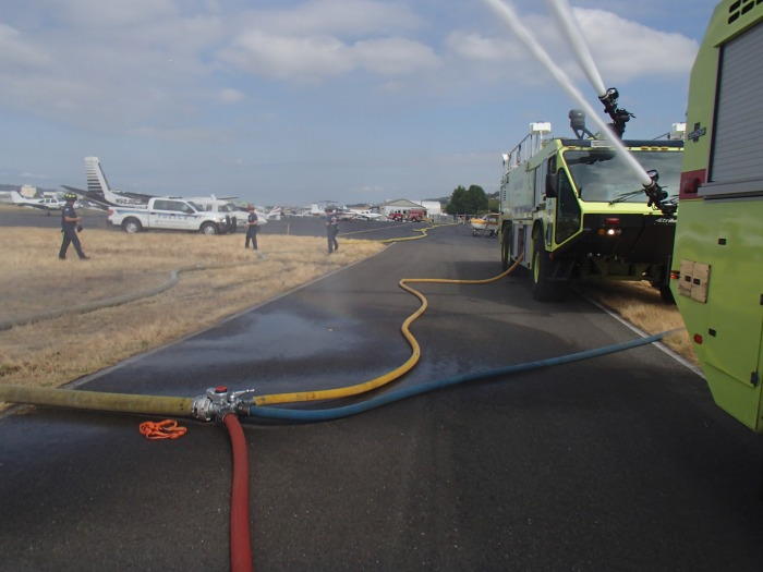 Fire trucks spray water during a multi-agency water training exercise in August at King County International Airport/Boeing Field.