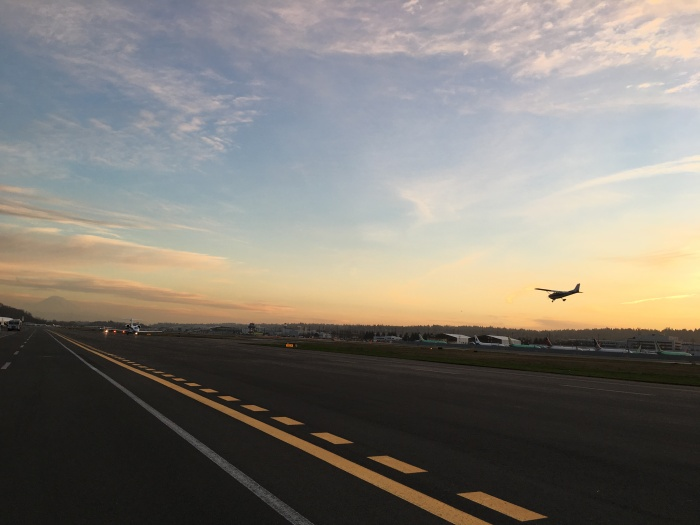 A plane lands on the Boeing Field Main Runway as the sun sets in the background.