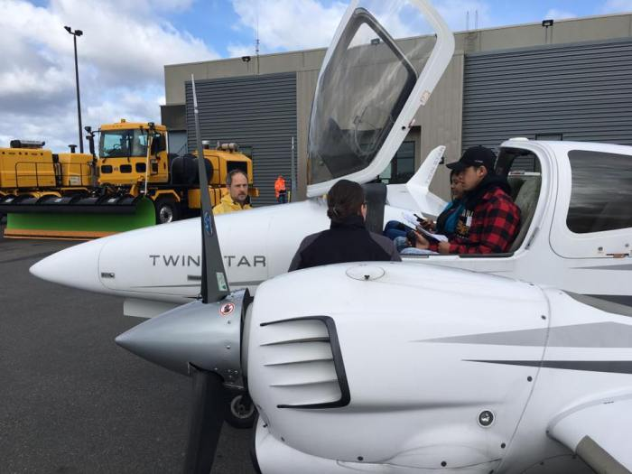 Students from Fostrer High School in Tukwila sit in the cockpit of a Diamond 42 aircraft while listening to a representative from Galvin Flying as part of DiscoverU on April 17, 2018.