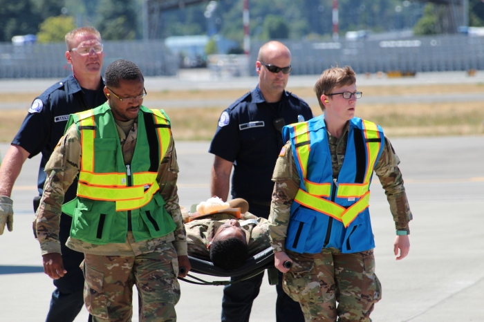 July 12, 2018 - As part of a fictional disaster exercise scenario, Military personnel and emergency responders carry a tsunami victim from a C-17 Globemaster to inside the Arrivals building at King County International Airport-Boeing Field.