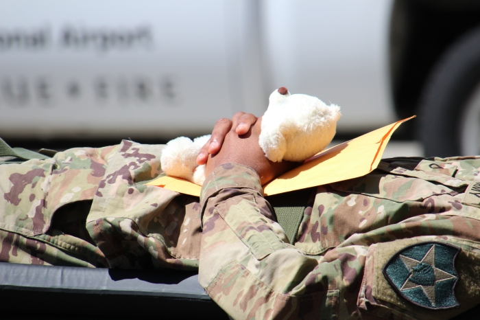 July 12, 2018 - As part of a fictional disaster exercise scenario, a victim clings to a teddy bear while being transferred from a C-17 Globemaster to inside the Arrivals building at King County International Airport-Boeing Field